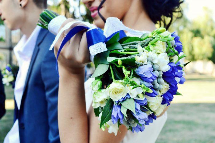 青い花のブーケを持つ新婦と新郎